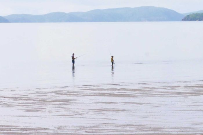Two men fish during low tide on Palm island with islands in the background