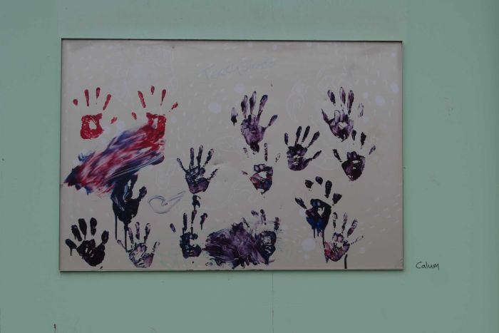Blue and red hands achieved with paint on a poster stuck to a building