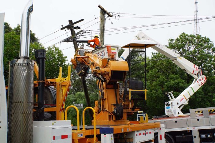 A workman in high vis uses a cherry picker to repair powerlines in a suburban street