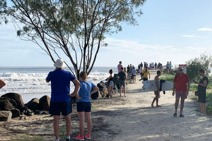 Crowd gathers to watch surf conditions at Kirra.