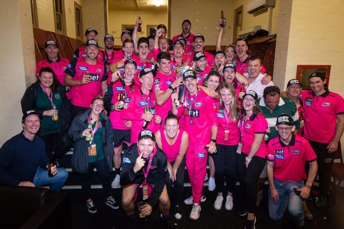 A group of men and women from the Sydney Sixers cheer and shout with bottles of beer in a changing room