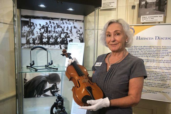 A woman wearing protective gloves holds a violin on display in a cabinet at a museum