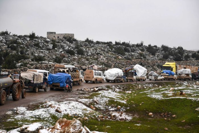 Syrian civilians flee from Idlib in rain toward the north to find safety inside Syria near the border with Turkey.