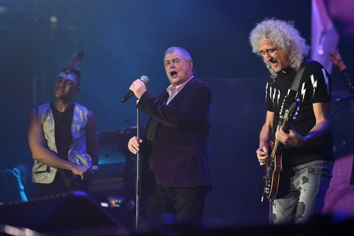 Mitch Tambo, John Farnham and Brian May perform on stage