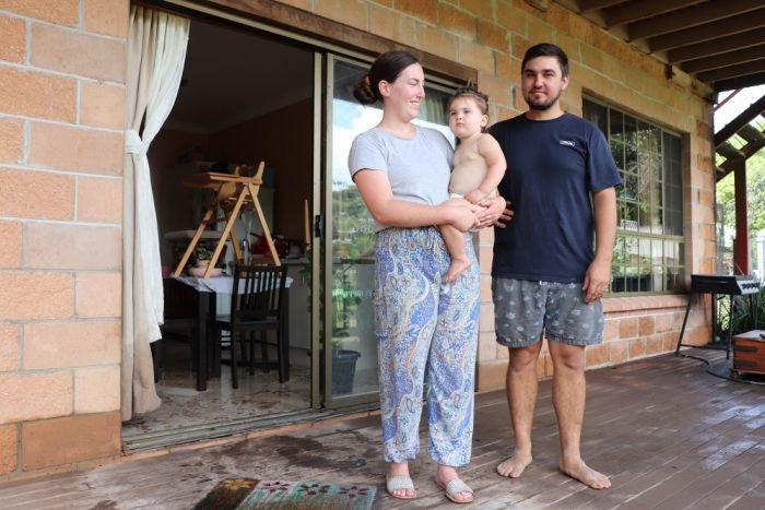Emily Campbell with fiance Jesse and baby Eden outside their home in Nana Glen to day after it was inundated by floodwater.