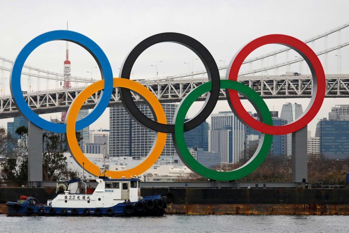 Giant versions of the five-coloured Olympic rings stand in front of a view of the city of Tokyo.