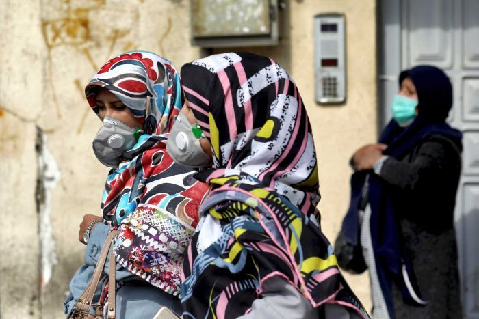 Women walk on the street wearing scarves and masks.