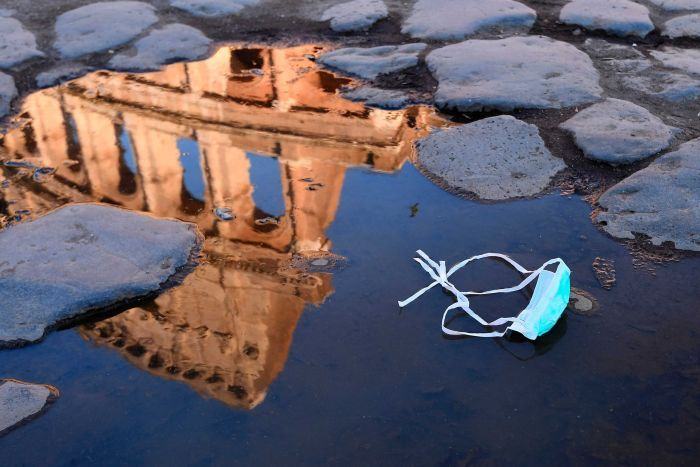 The Colosseum is reflected in a puddle, with a medical mask sitting on a cobblestone street.