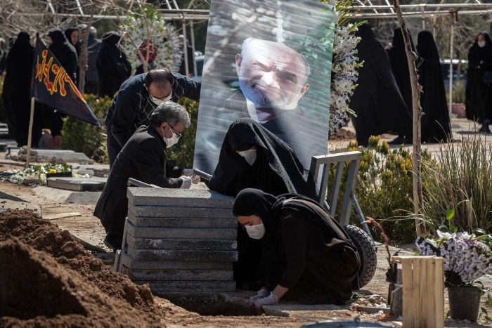 Relatives who wear face masks cry over the grave of a man whose photo is seen behind.