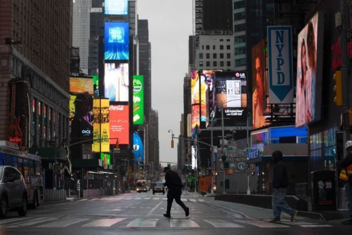 A man walks through Times Square, which is almost empty, which is usually very crowded on weekdays mornings.