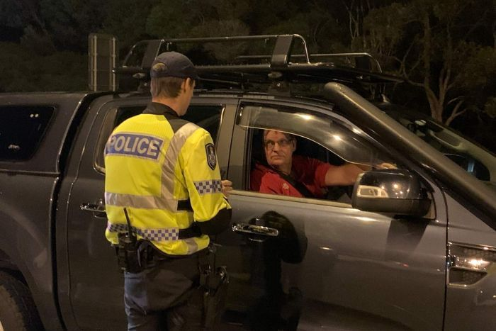 A policeman talking to a car driver in the darkness of early morning