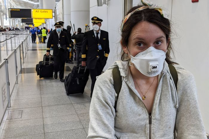Ed Coper's wife wearing a mask, in front of several pilots in masks, at JFK