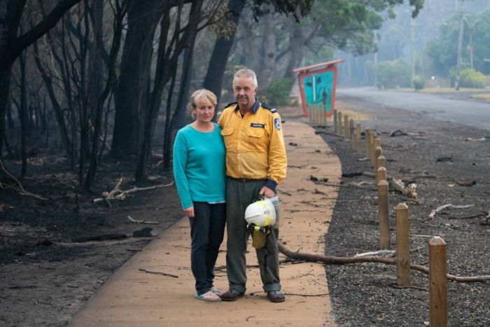 A man in a firefighters uniform and a woman pose with arms around one another on a footpath next to burnt out forest.