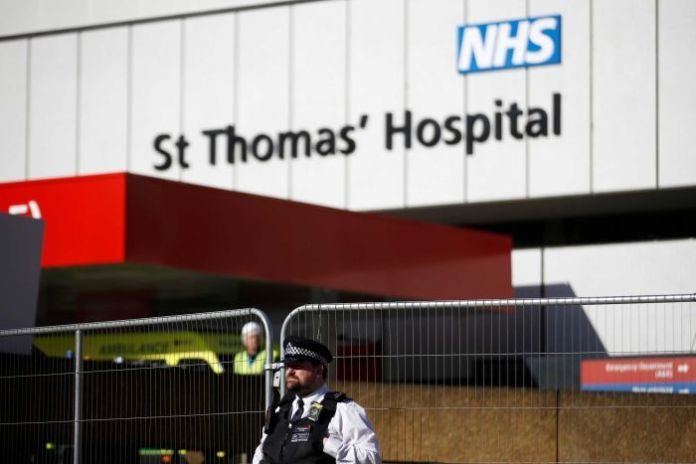A police officer stands outside the hospital building