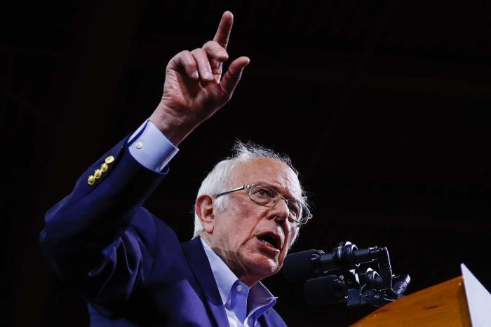 Bernie Sanders behind a podium with his arm up