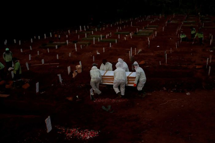 Five men wearing hazmat suits carry a coffin among a sea of freshly dug graves as grave diggers dig more graves.