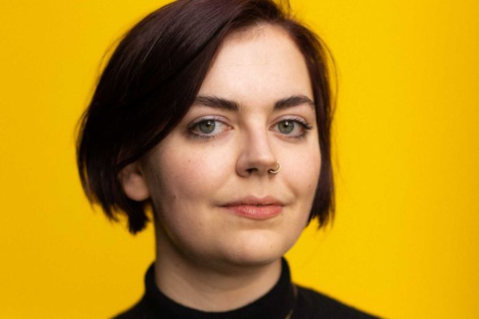 Portrait of a young woman, art historian Alice Procter, looking at the camera, yellow backdrop