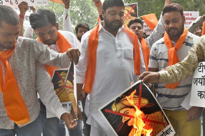 Men with orang scarves hold signs and set fire to a picture of Tipu Sultan with a red cross on it.