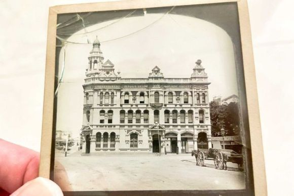 A hand holds up a glass slide photograph of a building in Brisbane in the 1800s.