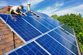 A tradesman is on top of a roof installing solar panels.
