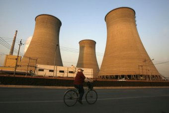 A woman rides her bicycle past a coal power station in Beijing.