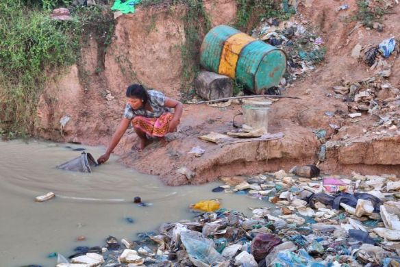 A woman fetches water at a Cambodian rubbish dump