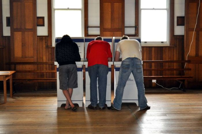 Three men vote at a Tasmanian polling station.