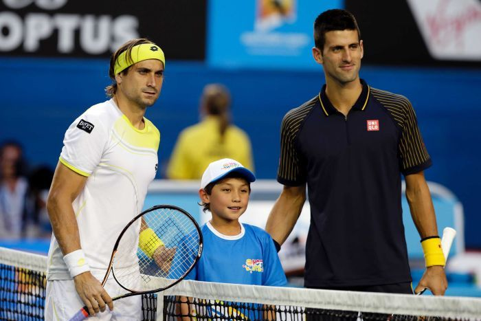 David Ferrer and Novak Djokovic pose for a photo with a boy before a tennis match.