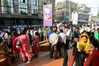 People stand outside buildings in Pakistan after powerful earthquake