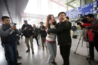A woman cries as she talks on her mobile phone at Beijing Capital International Airport