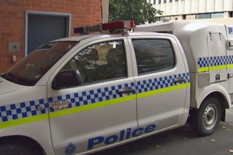 A police van takes Jassy and Michael Anglin into the Hobart police station after their extradition from Queensland.