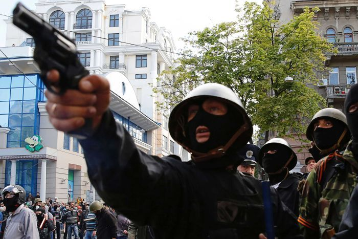A pro-Russian activist aims a pistol at supporters of the Kiev government during clashes in the streets of Odessa in 2014.