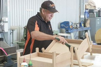 An older fellow busies himself with some woodwork in a tool shed.