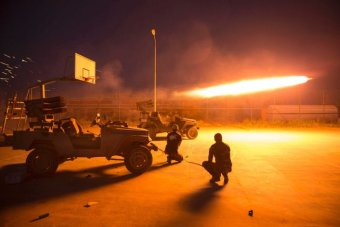 Shiite fighters fire a rocket during clashes with Islamic State