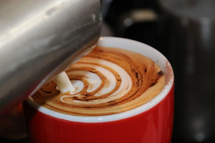 Coffee is seen being poured into a cup.
