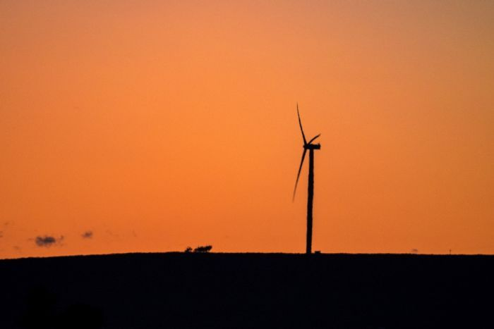 The silhouette of a single wind turbine on a hill at sunset