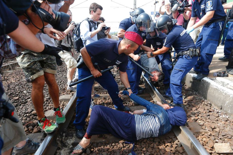 Hungarian policemen detain migrants on the tracks