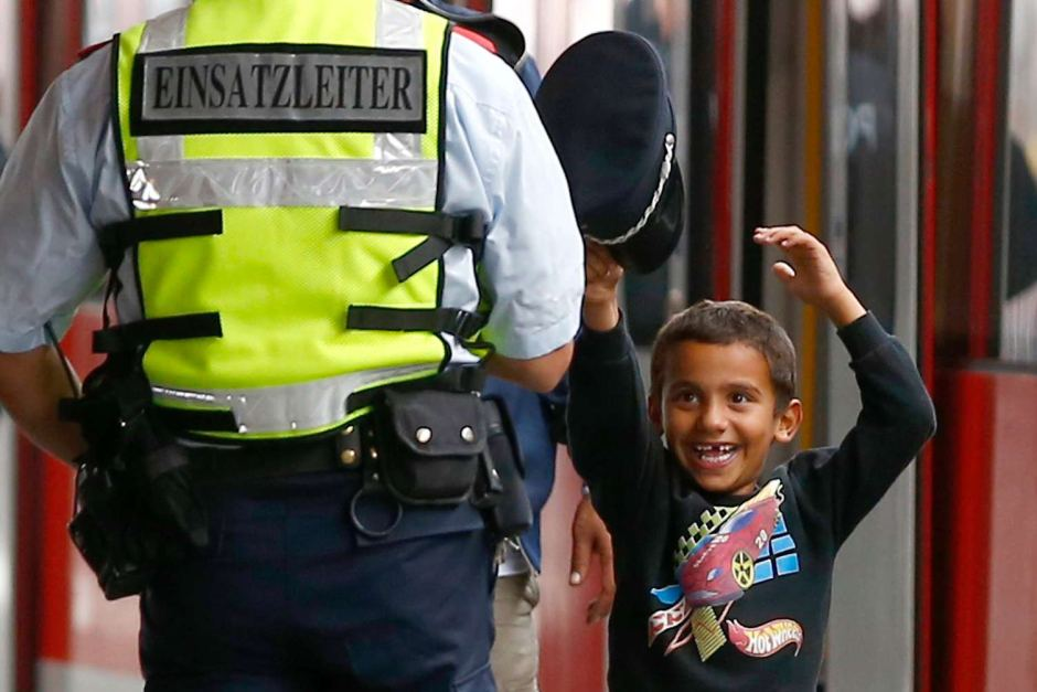 A young migrant boy tries on a Bahn security officer's cap