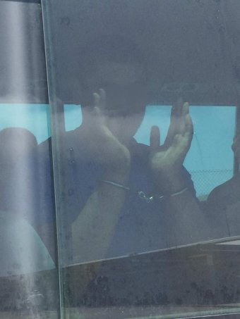 Christmas Island detainee in handcuffs after riot