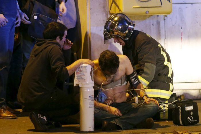 Firefighters aid an injured man near the Bataclan concert hall.