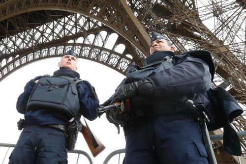 Police take up position under the Eiffel Tower the morning after a series of deadly attacks in Paris.