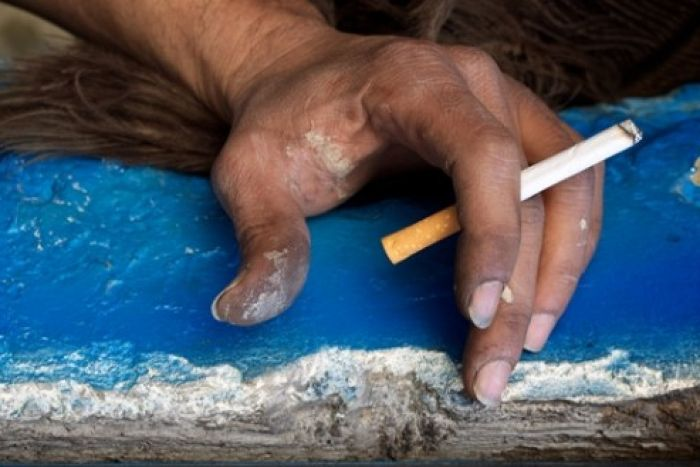 Photo of Indigenous hand holding a cigarette.
