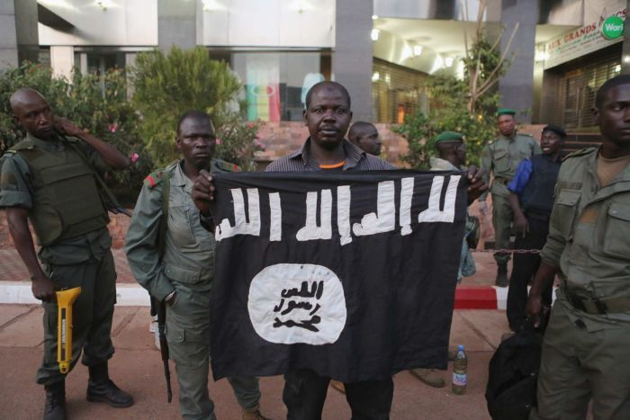 Malian security officials show a jihadist flag they said belonged to attackers in front of the Radisson hotel in Bamako, Mali