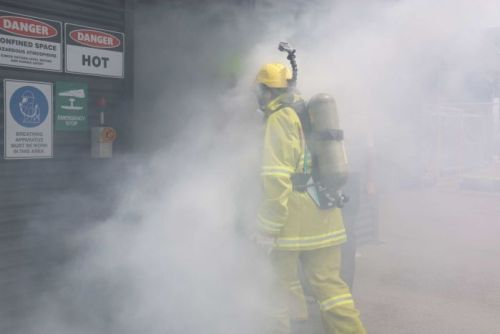 ABC News Canberra journalist Alkira Reinfrank enters a room filled with smoke.