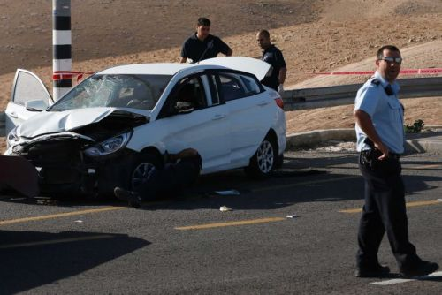 Israeli security forces stand around a crashed car.