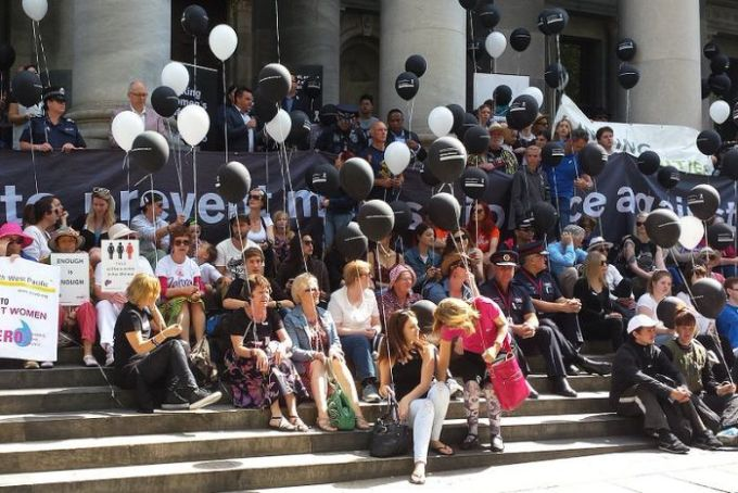 A crowd of people sit on Parliament House steps.