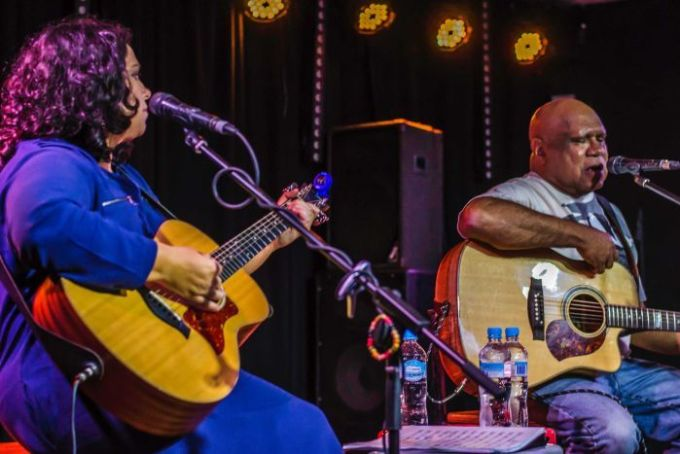 Nancy Bates and Archie Roach perform on stage holding guitars.