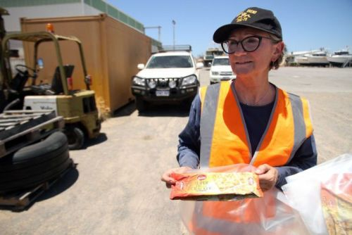 The WA Museum's head of maritime history, Sally May holding a packet of cracker biscuits found on the asylum seeker boat.
