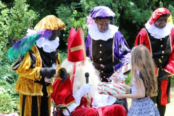 Saint Nicholas and Black Pete hand out presents to children at the Dutch Embassy. (7 December 2015)