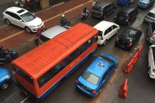 An orange Metro Mini private bus on the streets of Jakarta